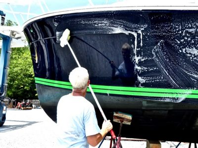 person washing the exterior of boat