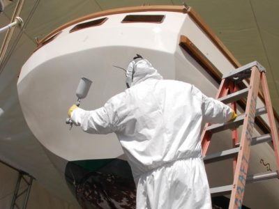 person painting the exterior of boat